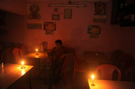 An Indian diner waits for his meal in candle light at a hotel during a power cut in Siliguri