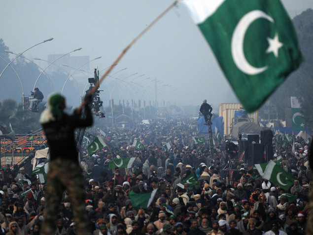 A supporter of preacher Tahir-ul Qadri waves a Pakistani flag at a protest rally in Islamabad on January 16, 2013