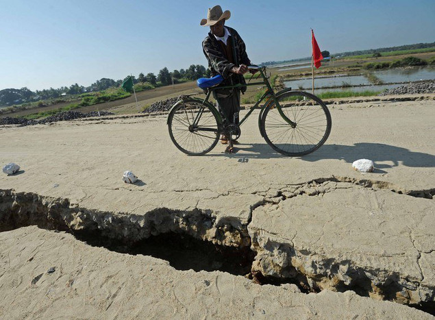 A villager looks at a crack in the road caused by an earthquake in Mandalay, central Myanmar, on November 12, 2012