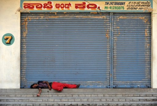 An Indian labourer sleeps in front of closed shops during a nationwide strike