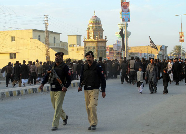 Policemen guard a Shiite procession in the Pakistani city of Dera Ismail Khan on November 25, 2012