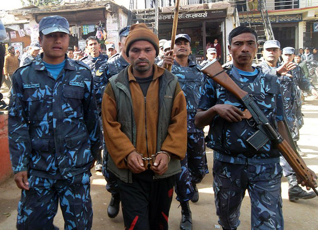 Nepalese police escort ex-Maoist rebel Lachhiram Gharti after arresting him in Dullu, Dailekh district, January 6, 2013