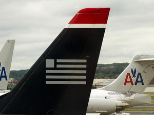 A US Airways tail rests on the tarmac near two American Airlines planes at Ronald Reagan Washington National Airport in Arlington, Virginia in this April 23, 2012