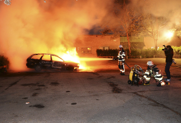 Firefighters extinguish a burning car in the Stockholm suburb of Kista