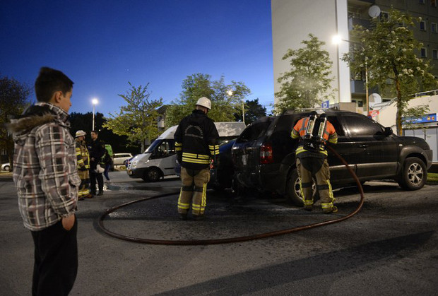 Firemen extinguish a burning car in the Stockholm suburb of Tensta after youths rioted on May 24, 2013