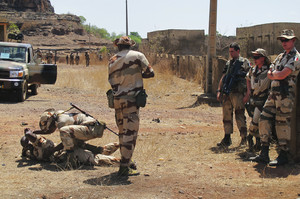 French soldiers, part of the European Union training mission in Mali, look on as Malian soldiers practise manning a checkpoint and arresting a suspect in Koulikoro