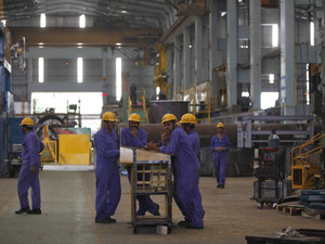 Employees gather after a lunch break inside the heavy electrical manufacturing unit of Larsen & Turbo in Mumbai