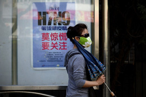 A woman walks past a poster showing how to avoid the H7N9 bird flu virus, in Beijing on April 24, 2013