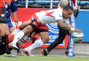 Tonga's Fetuu Vainikolo (centre) dives to score a try against Japan in Yokohama, May 25, 2013