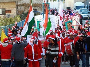 Asian Christian worshipers wearing Santa Claus costumes march to the Church of the Nativity in the West Bank town of Bethlehem on December 18, 2013