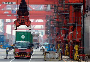 Workers load containers onto a cargo ship at a pier in Tokyo on May 10, 2013