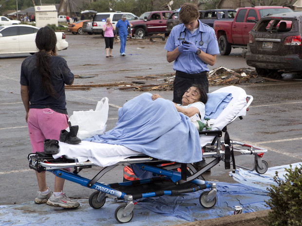 A woman is tended to by a Emergency Medical Technician after a huge tornado struck Moore, Oklahoma