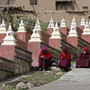 Tibetan monks sit at an entrance to the Dzamthang Jonang monastery in Barma township