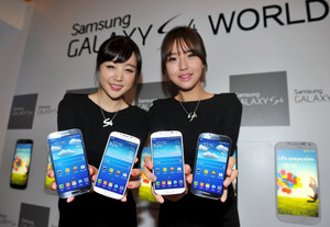 Samsung Electronics employees display the new Galaxy S4 smartphones during an event in Seoul on April 25, 2013