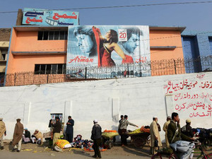 Pakistani street vendors and pedestrians gathered outside the Shama cinema in Peshawar, on December 19, 2013