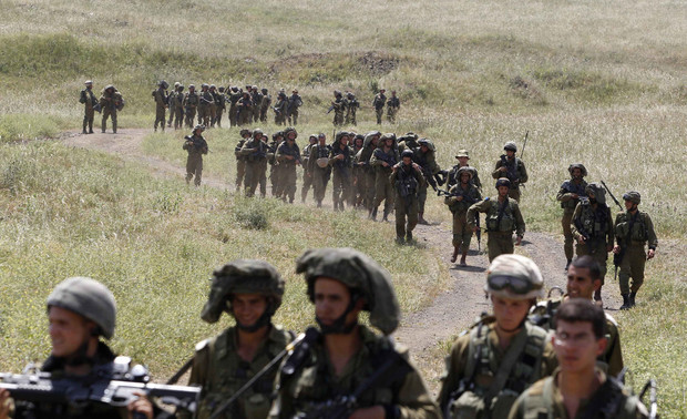 Israeli soldiers walk together during training close to the ceasefire line between Israel and Syria on the Golan Heights