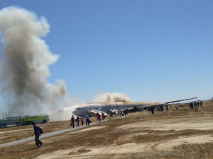 Passengers evacuate from Asiana Airlines Boeing 777 aircraft after a crash landing at San Francisco International Airport in San Francisco