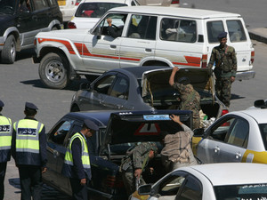 Police troopers inspect cars at checkpoint near Defence Ministry compound in Sanaa