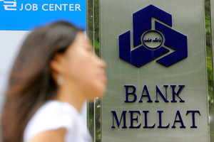 A woman passes a branch of Bank Mellat in Seoul on September 8, 2010