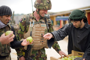 A British soldier (C) and his interpreter (L) talk with an Afghan actor, at a military base in Norfolk, on June 10, 2009