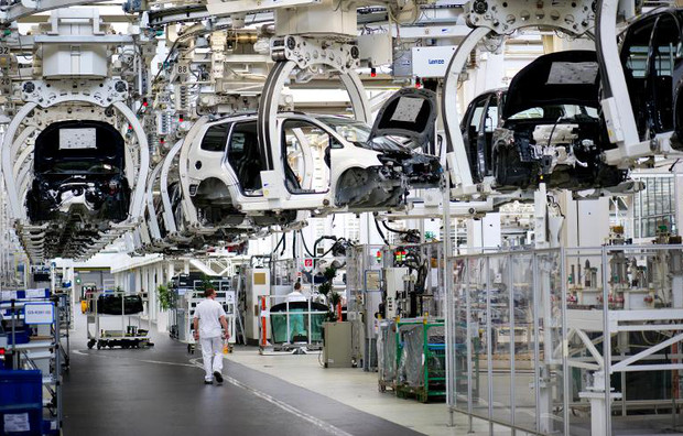 Partly built Volkswagen cars travel overhead at the assembly line for the VW Tiguan and Touran models in Wolfsburg on March 7, 2012