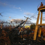 Men sit atop a structure and watch the sunrise in an devastated area at Tacloban City