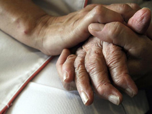 A nurse holds a patient's hands at a retirement home in eastern France, on September 21, 2009