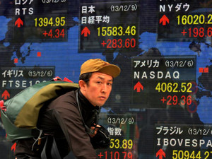 A cyclist passes a share prices board in Tokyo on December 9, 2013