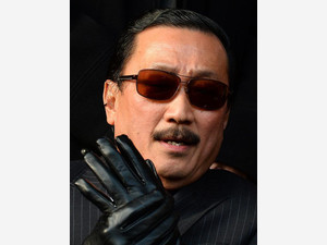 Cardiff City's Malaysian owner Vincent Tan puts his gloves on before the club's English Premier League football match against Liverpool in Liverpool on December 21, 2013