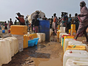 South Sudanese women queue for water being distributed at the United Nations Mission in South Sudan compound in Juba on December 21, 2013