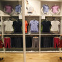 A woman looks at shirts displayed at a casual clothing store in Tokyo