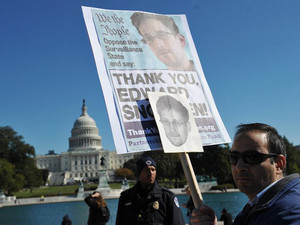 Demonstrators hold placards supporting former US intelligence analyst Edward Snowden during a protest against government surveillance on October 26, 2013 in Washington, DC