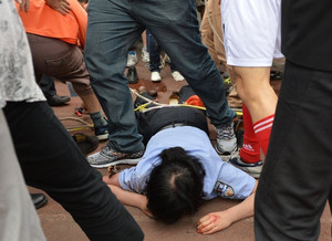 A policewoman lies on the floor after being crushed during a stampede at Tonji University in Shanghai, on June 20, 2013