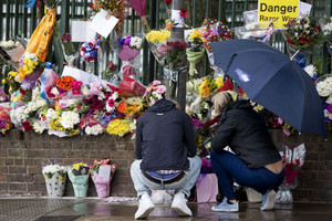 People look at floral tributes left at the scene where Lee Rigby was killed outside Woolwich Barracks in London