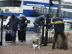 Passengers in the harbor of Harlingen, The Netherlands, struggle against the wind on December 5, 2013 after arriving by ferry from the Frisian island Vlieland