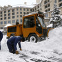 Workers clear snow off an ice skating rink in Beaver Creek