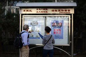 Two tourists look at a poster showing how to avoid the H7N9 bird flu virus in Beijing on April 24, 2013