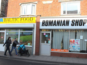 A couple walk past shops catering for eastern Europeans in Boston, in Lincolnshire, eastern England, on February 19, 2013