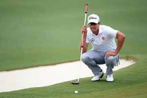 Adam Scott lines up a putt with his broom-handle putter at Augusta National Golf Club on April 14, 2013