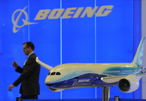A man walks past a model of a Boeing 787 at the aerospace exhibition in Hong Kong on March 8, 2011