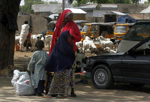 Woman and two children stand along Jos-Maiduguri road as they wait to board vehicle, after military declared 24-hour curfew over large parts of Maiduguri in Borno State