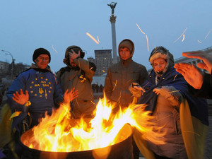 Pro-EU opposition demonstrators try to warm themselves near a bonfire on Independence Square in Kiev, early on December 6, 2013