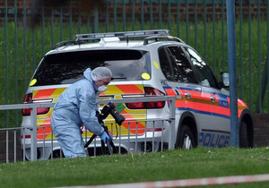 A police forensics officer takes photographs inside a cordoned off area in Woolwich, east London, on May 22, 2013