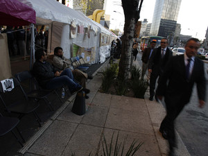 Employees walk past demonstrators sitting outside tents during a protest against an energy reform bill outside the Senate building in Mexico City