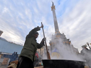 An activist cooks in a camp set by opposition demonstrators in Kiev's Independence Square on December 4, 2013