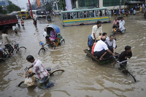 Bangladeshi pedestrians and rickshaw pullers travel through flooding in the Bangladeshi capital Dhaka on July 28, 2009
