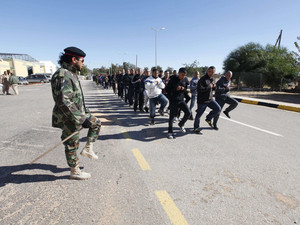 A Libyan army soldier watches as recruits train in Tripoli