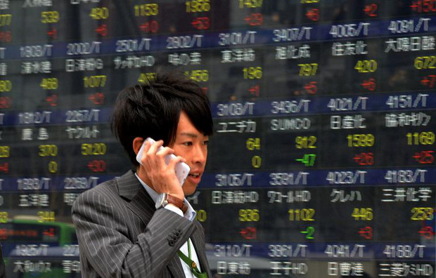 A businessman passes a share prices board in Tokyo on December 9, 2013