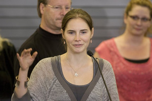 Amanda Knox waves to supporters at SeaTac Airport after arriving in Seattle on October 4, 2011
