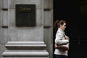 A woman walks past Telefonica's building in central Madrid